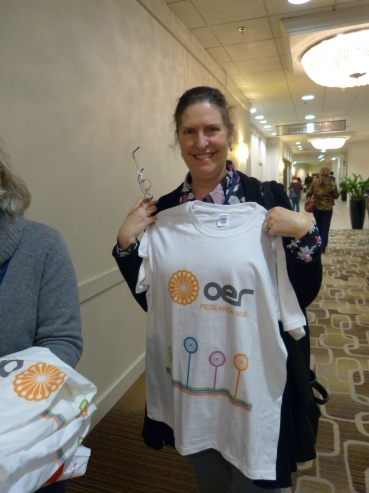 Cheryl (ROER4D) modelling our new T-Shirts! (CC-BY 4.0 OER Research Hub)